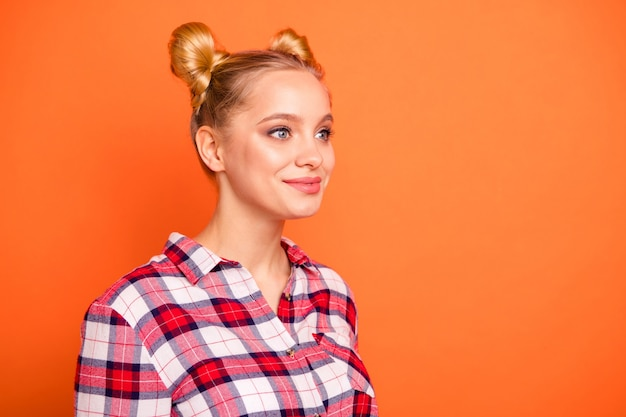 Портрет молодой женщины, одетой в клетчатую рубашку, изолированную на оранжевом