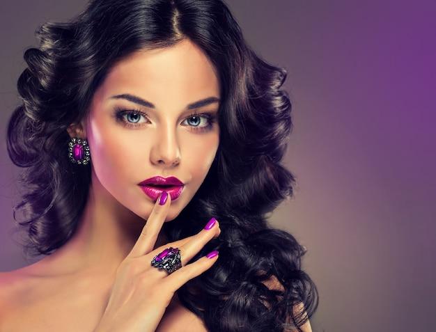 Портрет молодой женщины, одетой в великолепный вечерний макияж. идеальная густая, волнистая прическа. макияж, маникюр и украшения в фиолетовых тонах. парикмахерское искусство, уход за волосами и макияж.