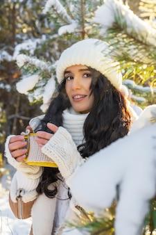 冬の森で温かい飲み物を飲む若い女性の肖像画