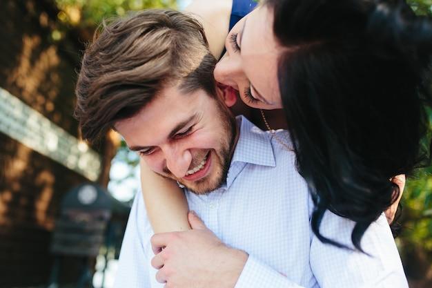 Портрет молодой женщины, обнимая своего парня сзади