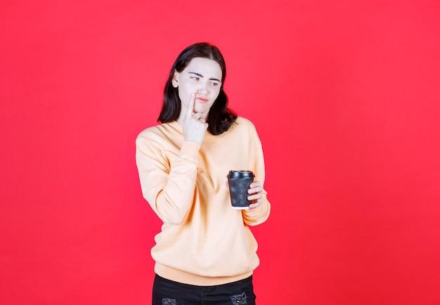 빨간 backgroung에 고립 된 찻잔 커피를 껴 안은 젊은 여자의 초상화
