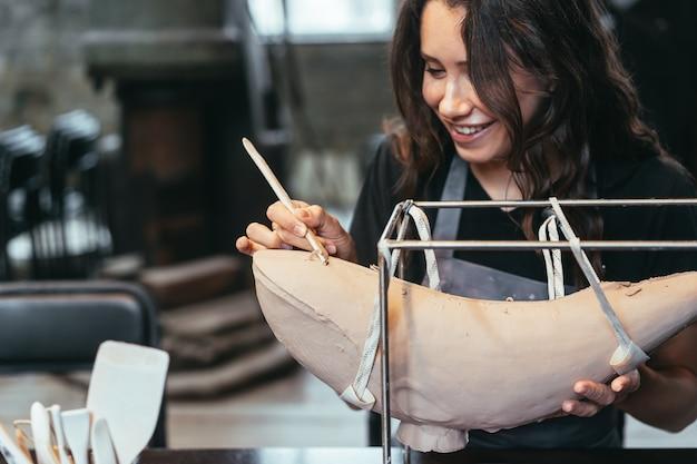 Портрет молодой женщины, наслаждающейся любимой работой в мастерской. гончар тщательно работает над глиняным китом
