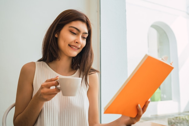 Портрет молодой женщины, наслаждающейся свободным временем и читающей книгу, сидя на открытом воздухе в кафе