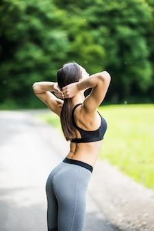 Портрет молодой женщины, тренирующейся в парке.