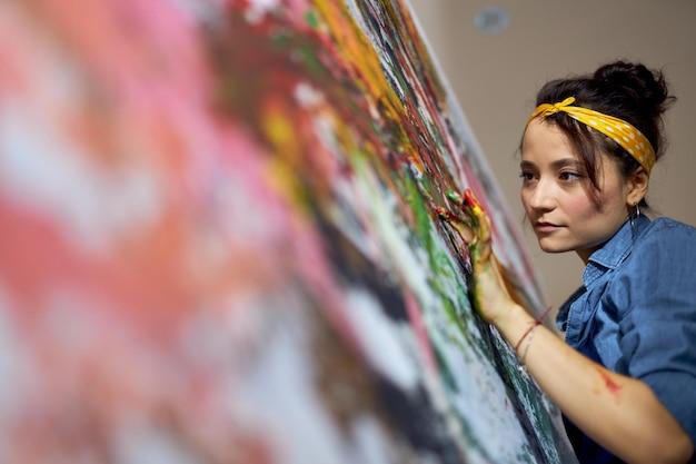 大きなを作成しながら指でキャンバスにペイントを適用する若い女性の女性画家の肖像画