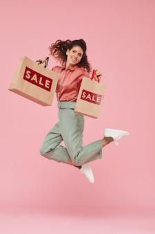 Портрет молодой женщины, довольной своей успешной покупкой, она прыгает на розовом фоне