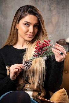 クリスマスのヒイラギの果実の枝を保持している若い女性の肖像画。高品質の写真
