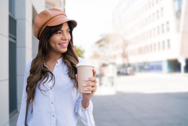 通りを屋外で歩いている間コーヒーを保持している若い女性の肖像画。アーバンコンセプト。