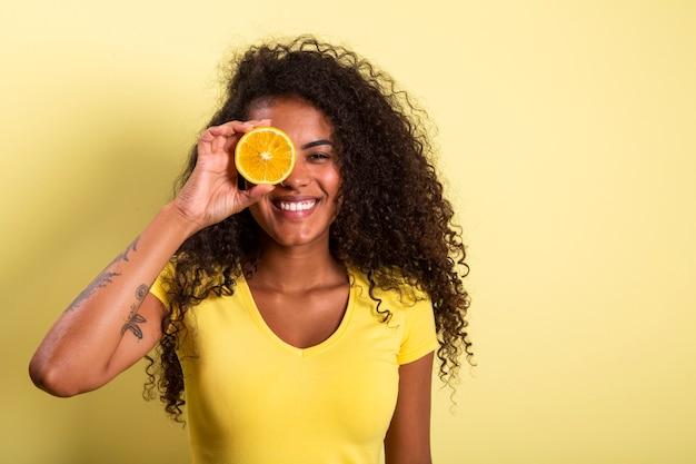 그녀의 눈에 오렌지를 들고 젊은 여자의 초상화. 카메라를보고 여성 모델