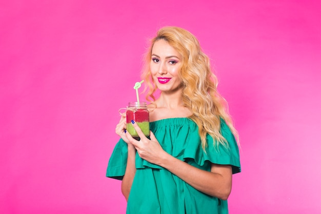 ピンクの背景においしい緑のスムージーミルクセーキを保持し、飲んで若い女性の肖像画