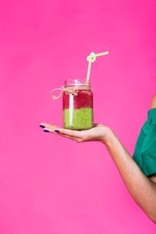 ピンクの壁においしい緑のスムージーミルクセーキを保持し、飲んでいる若い女性の肖像画。