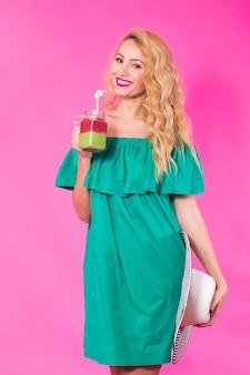 ピンクのおいしい緑のスムージーミルクセーキを保持し、飲んで若い女性の肖像画
