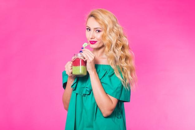 おいしい緑のスムージーを保持し、飲む若い女性の肖像画