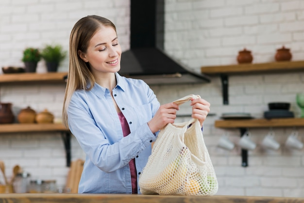 Портрет молодой женщины, держащей сумку со свежими фруктами