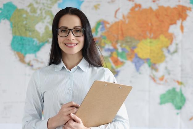 Портрет молодой женщины, держащей буфер обмена с документами на фоновой карте мира