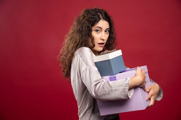 선물 상자를 단단히 들고 젊은 여자의 초상화.