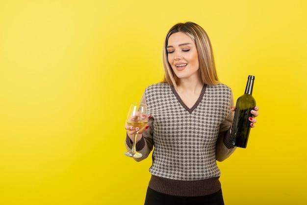 Портрет молодой женщины, держащей стакан и бутылку белого вина.