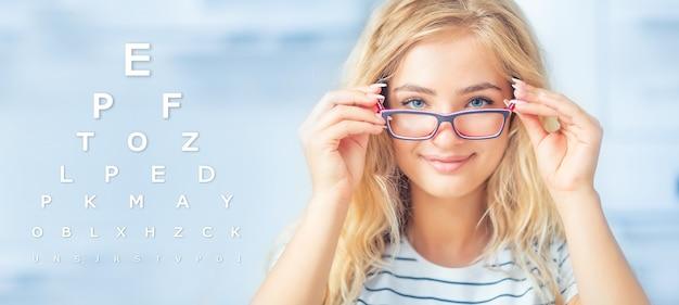 안경을 들고 카메라를 보고 있는 젊은 여성의 초상화. 눈 검사 차트가 있는 안과 개념.