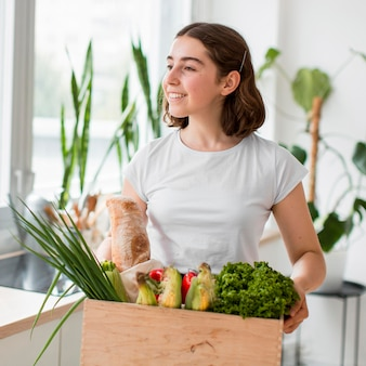 Портрет молодой женщины, держащей органические овощи