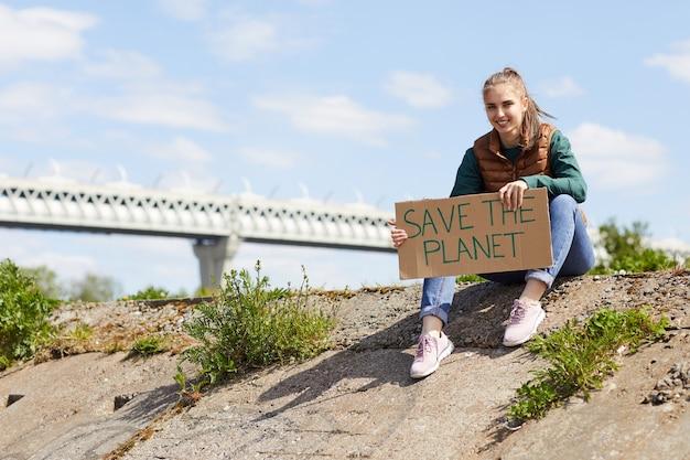 プラカードを持って、屋外の岩の上に座ってカメラに笑顔の若い女性の肖像画