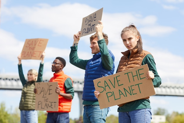 Портрет молодой женщины, держащей плакат со своими друзьями на заднем плане, пока они стояли на открытом воздухе