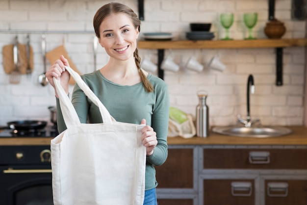 Портрет молодой женщины, держащей многоразовую сумку