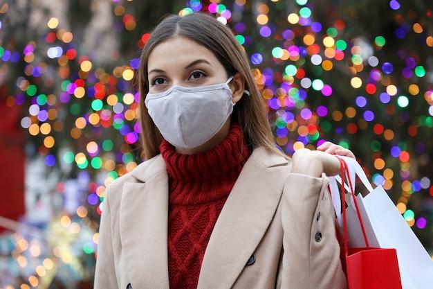 木のクリスマスライトと街の通りを歩く買い物袋を保持している若い女性の肖像画