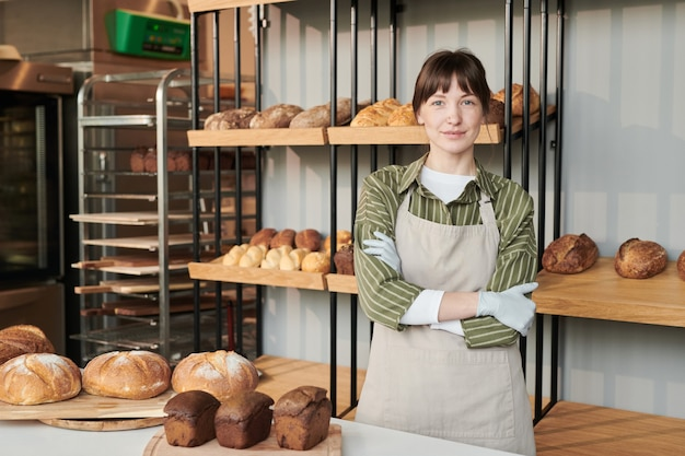Портрет молодой женщины в фартуке, смотрящей в камеру, стоя в пекарне со свежим хлебом на заднем плане