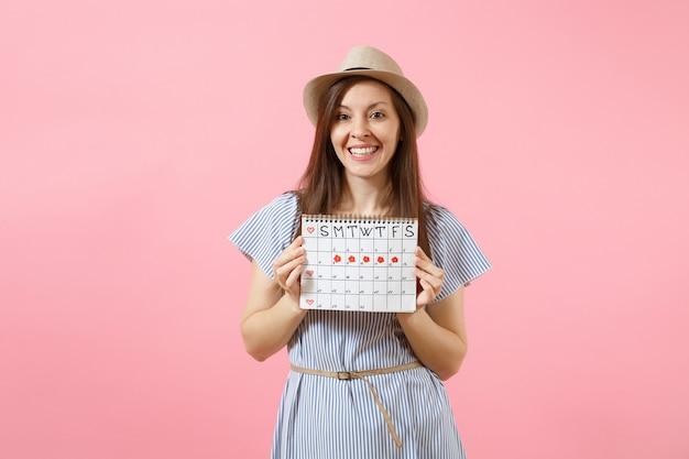 파란 드레스를 입은 젊은 여성의 초상화, 밝은 분홍색 배경에 격리된 월경일을 확인하기 위한 기간 달력을 들고 있는 모자. 의료, 건강 관리, 부인과 개념입니다. 공간을 복사합니다.