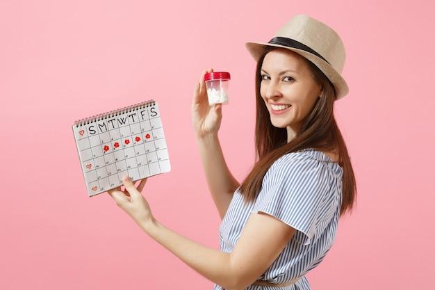 흰색 알약, 여성 기간 달력, 배경에 격리된 월경일을 확인하는 병을 들고 파란 드레스를 입은 젊은 여성의 초상화. 의료 의료 부인과 개념입니다. 공간을 복사합니다.