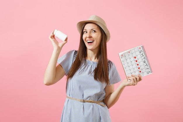 알약, 여성 기간 달력, 배경에 고립 된 월경 날짜를 확인 하는 흰색 병을 들고 파란 드레스에 젊은 여자의 초상화. 의료 의료 부인과 개념입니다. 공간을 복사합니다.