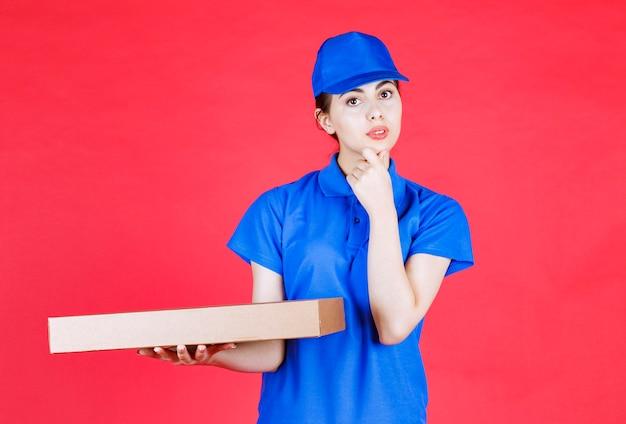 赤い壁の上の段ボール箱でポーズをとって青い服を着た若い女性の肖像画。