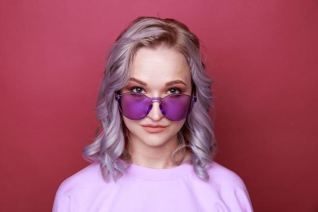 ピンクの背景の上に孤立して立っている明るいメガネの若い女性の肖像画