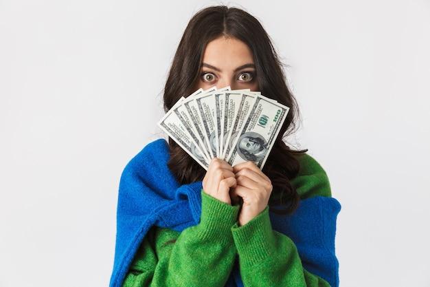 白で隔離されて立っている間、ドルのお金のファンを保持しているカジュアルな服を着た若い女性の肖像画