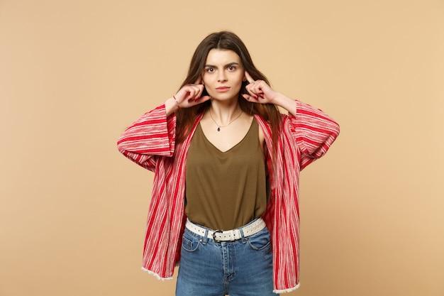 スタジオでパステルベージュの壁の背景に分離された指で耳を覆う、カメラを探しているカジュアルな服を着た若い女性の肖像画。人々の誠実な感情、ライフスタイルのコンセプト。コピースペースをモックアップします。