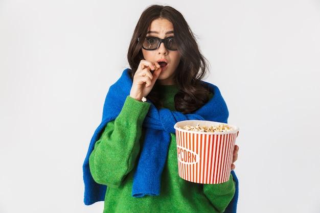 Портрет молодой женщины в повседневной одежде в 3d-очках, едящей попкорн из ведра, стоя изолированной на белом