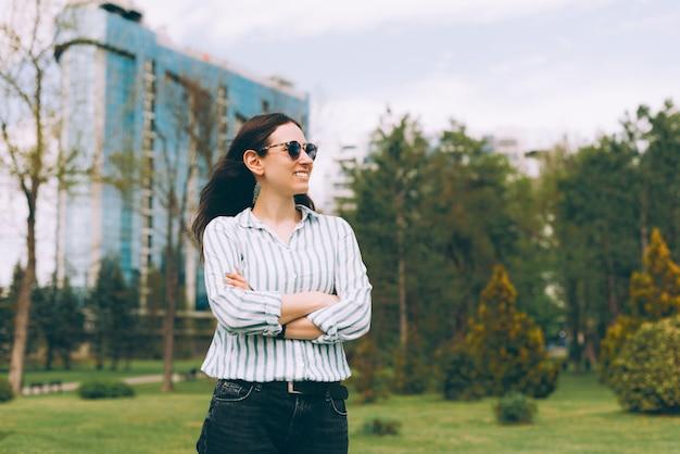 Портрет молодой женщины в непринужденной обстановке на открытом воздухе в городе и глядя в сторону
