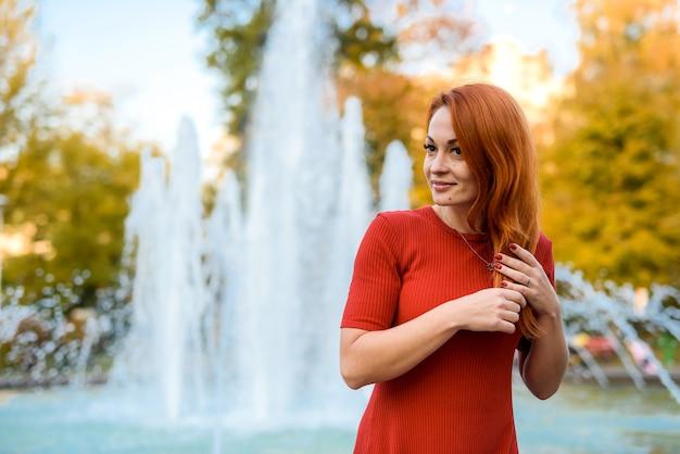 Портрет молодой женщины в повседневной одежде, позирующей возле фонтана на открытом воздухе
