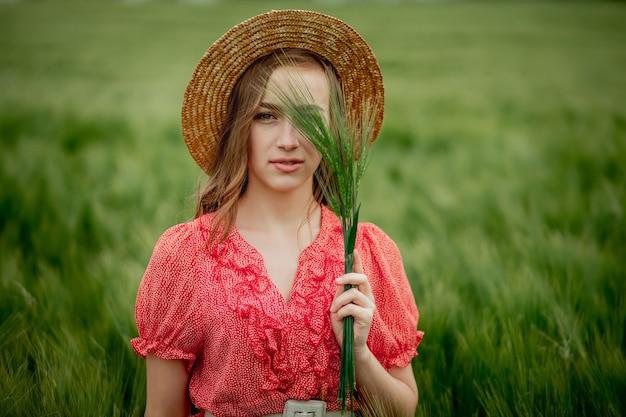 Портрет молодой женщины в платье и шляпе в зеленом поле ячменя в сельской местности