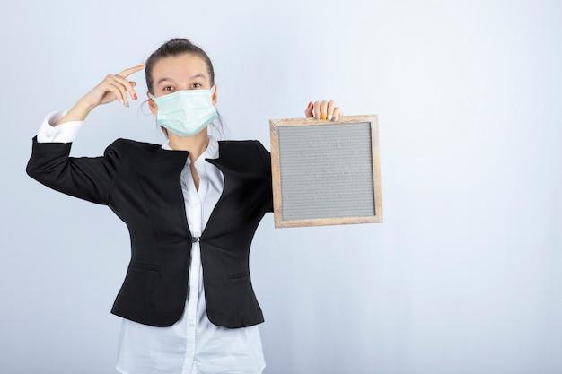 白い壁の上のフレームを保持しているフェイスマスクの若い女性の肖像画。高品質の写真