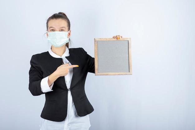 Портрет молодой женщины в лицевой маске, держащей рамку над белой стеной. фото высокого качества