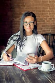 メガネの若い女性の肖像画は、スマートフォンでカフェに座っているし、カメラ目線のプランナーに書き込みます。
