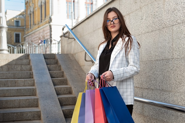 Портрет молодой женщины в куртке и очках с разноцветными бумажными пакетами. студент после покупок.