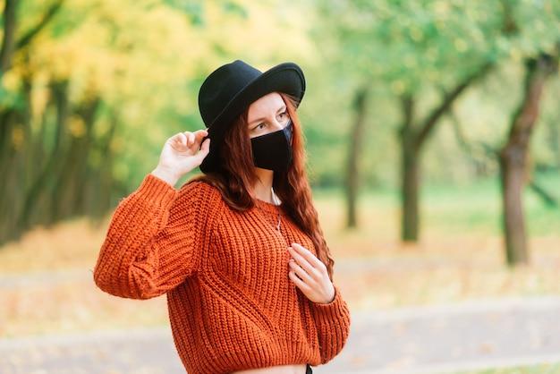 ニットの赤いセーター、秋の黄色い公園で黒のスタイリッシュな医療マスクの帽子の若い女性の肖像画。ファッション、ライフスタイル、検疫、コロナウイルス。