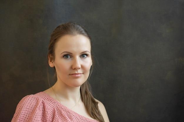 明るいピンクのブラウスと暗い背景の若い女性の肖像画