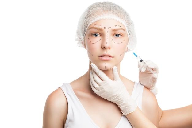 얼굴에 주사기가 주입되는 의료 모자를 쓴 젊은 여성의 초상화. 스튜디오 촬영
