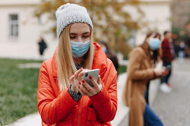 路上で現代のスマートフォンを使用して医療マスクの若い女性の肖像画。屋外の距離に立っている人々のぼやけた背景。