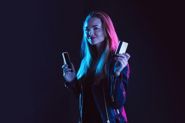 暗い背景にネオンの光の若い女性の肖像画。人間の感情、ブラックフライデー、サイバーマンデー、購入、販売、財務の概念。
