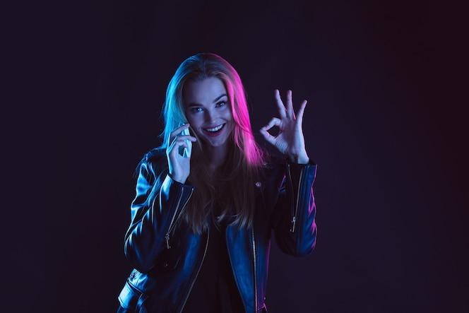 暗い背景にネオンの光の若い女性の肖像画。