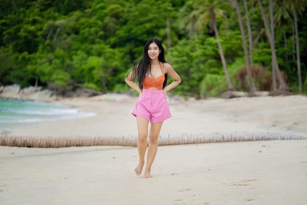 열 대 해변에서 오렌지 비키니 입은 젊은 여자의 초상화